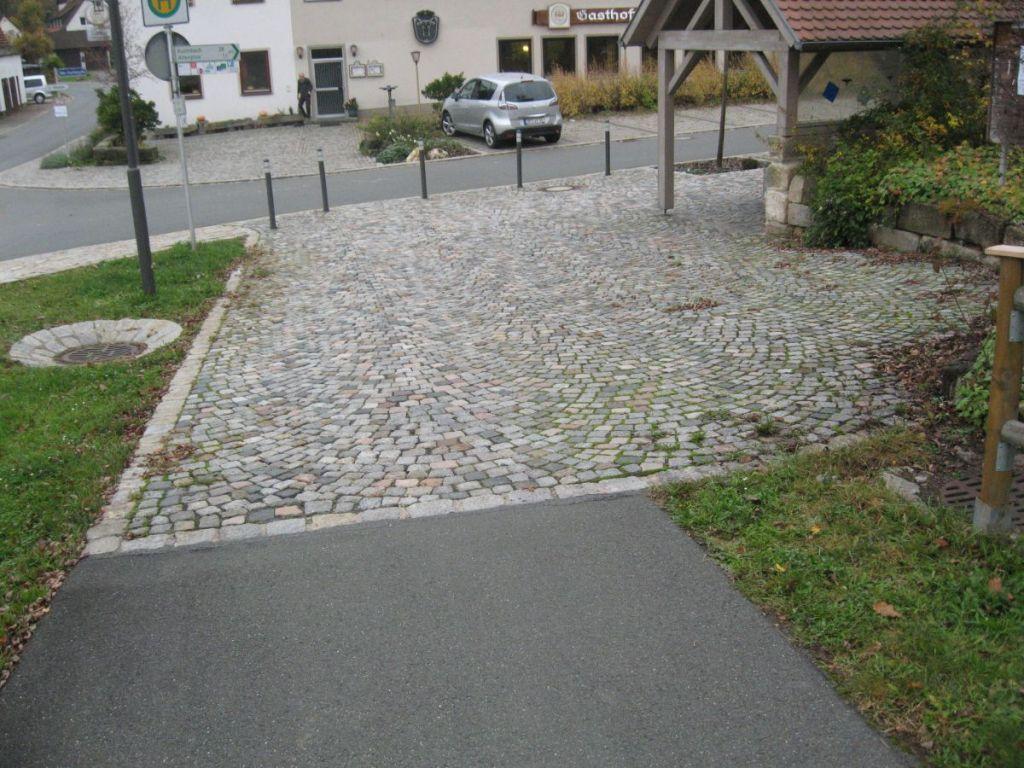 Kopfsteinpflaster, dunkle Absperrpfosten und Bordstein.